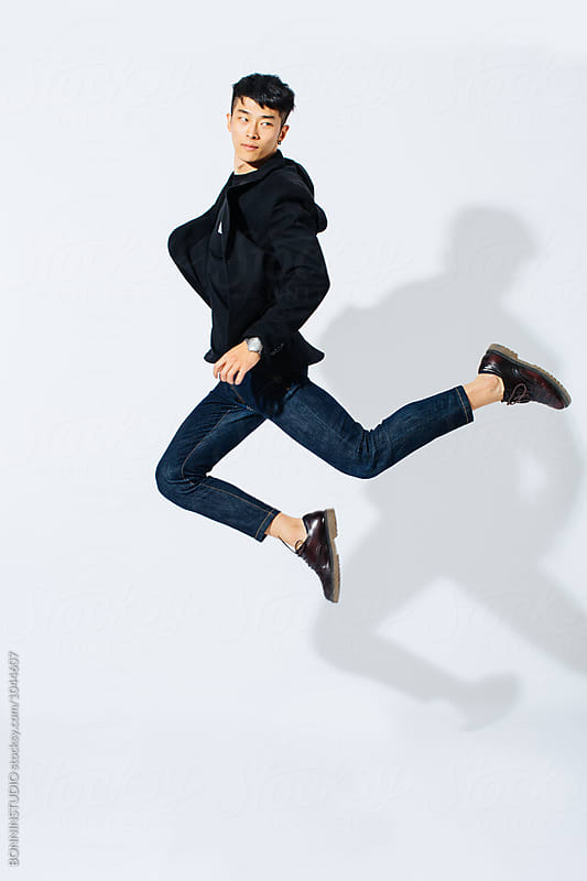 Jumping stylish asian man over white background. by BONNINSTUDIO for Stocksy United