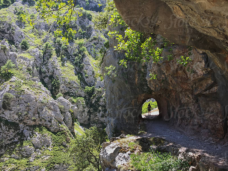 Hiker passing in a tunnel on a mountain trail by Luca Pierro for Stocksy United
