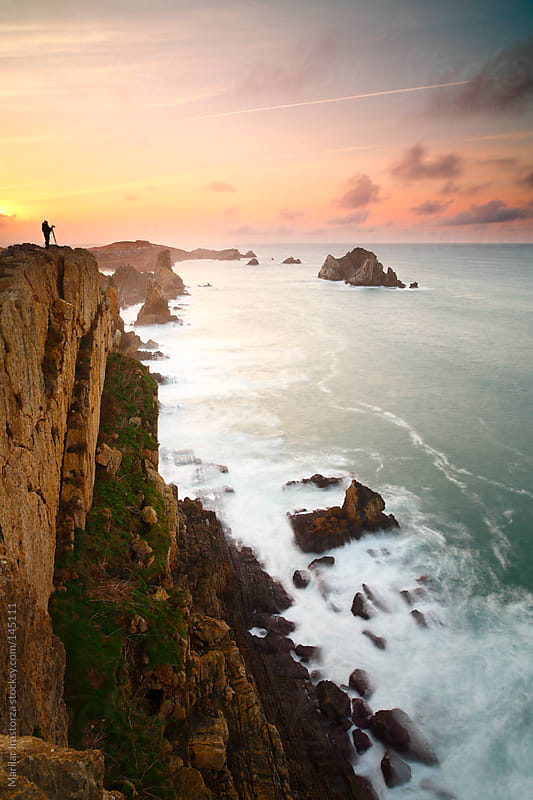 A landscape photographer photographing a seascape from a cliff  by Marilar Irastorza for Stocksy United