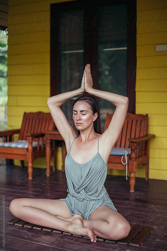Woman doing yoga on a porch by Studio Firma for Stocksy United