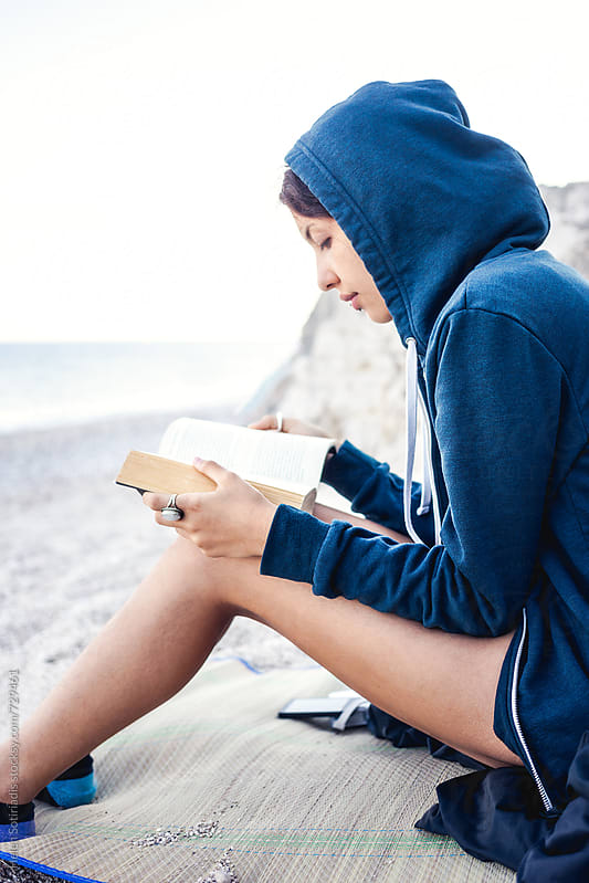 Young Woman Reading on the Beach by Helen Sotiriadis for Stocksy United