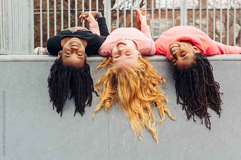 Upside down African American and Caucasian girls by Gabriel (Gabi) Bucataru for Stocksy United