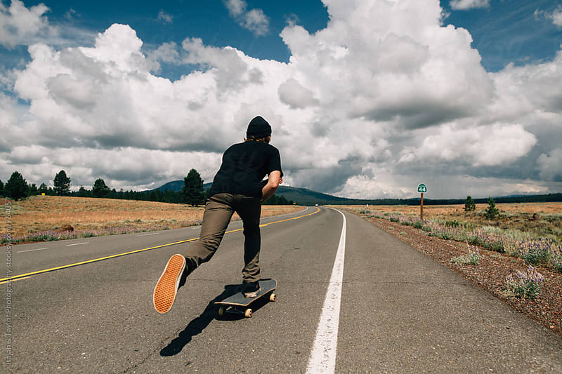 Skateboarder cruising down highway by Isaiah & Taylor Photography for Stocksy United