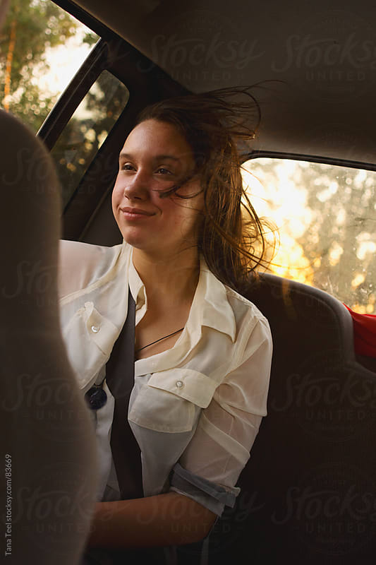Girl sitting in back seat of car with wind blowing her hair by Tana Teel for Stocksy United