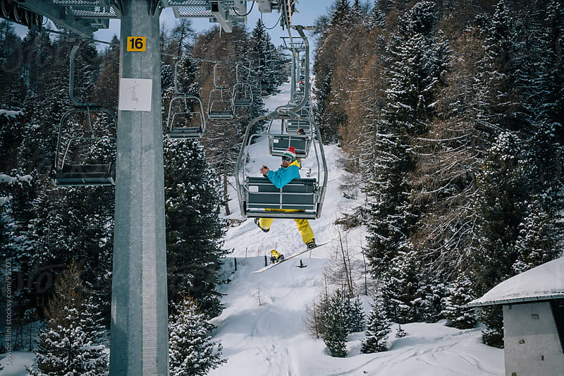 Snowboarder on the chairlift by Davide Illini for Stocksy United