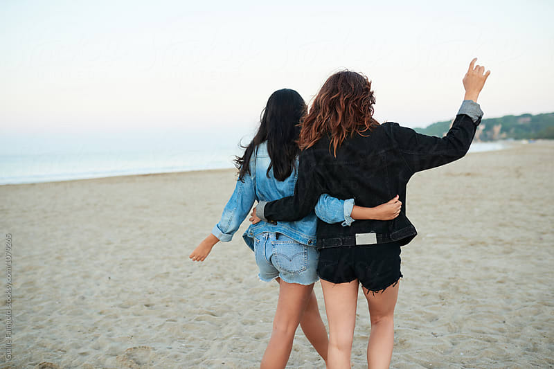 Girlfriends walking on beach by Guille Faingold for Stocksy United