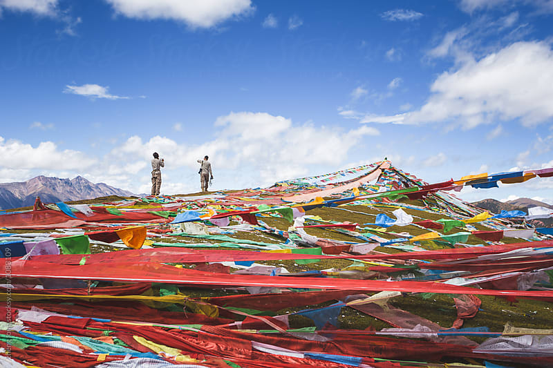 young couple take picture stand beside prayer flags  by zheng long for Stocksy United