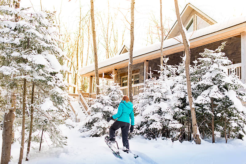 Woman with Snowshoes at Cottage in Winter With Snow by JP Danko for Stocksy United