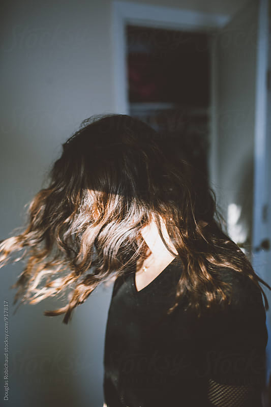 Girl winging hair in ambient lighting by Douglas Robichaud for Stocksy United