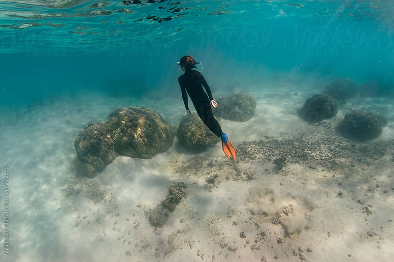 Child in a wet suit and snorkel set free dives amongst the coral on the Ningaloo Coast in Western Australia by Angela Lumsden for Stocksy United