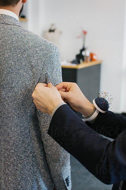 Close Up of Caucasian Tailor's Hands Using Fixing Pins on Customer's Suit by Julien L. Balmer for Stocksy United