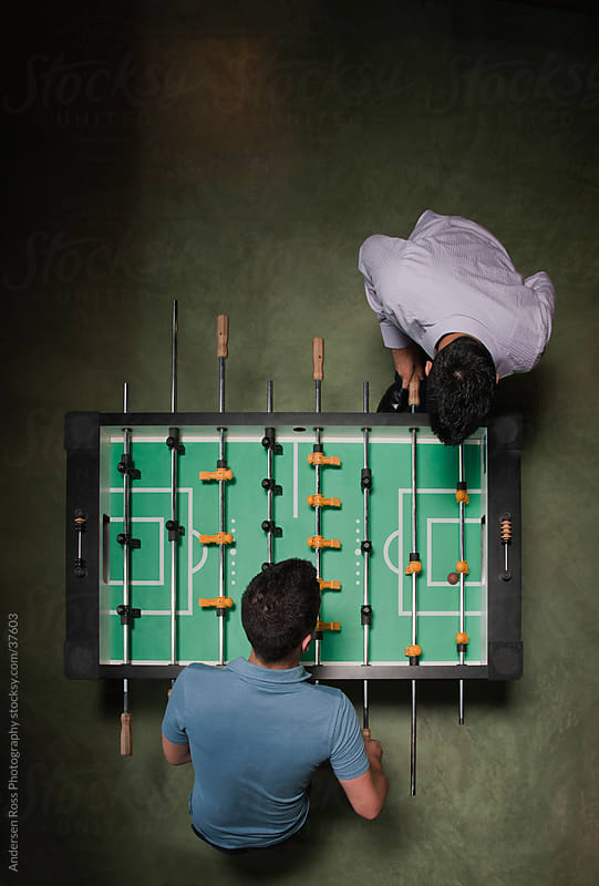 Overhead view of two men playing foosball by Andersen Ross Photography for Stocksy United