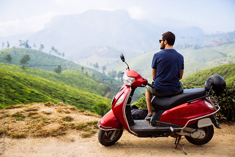 Young man sitting on a red moped looking at scenic view on the mountain by Alejandro Moreno de Carlos for Stocksy United