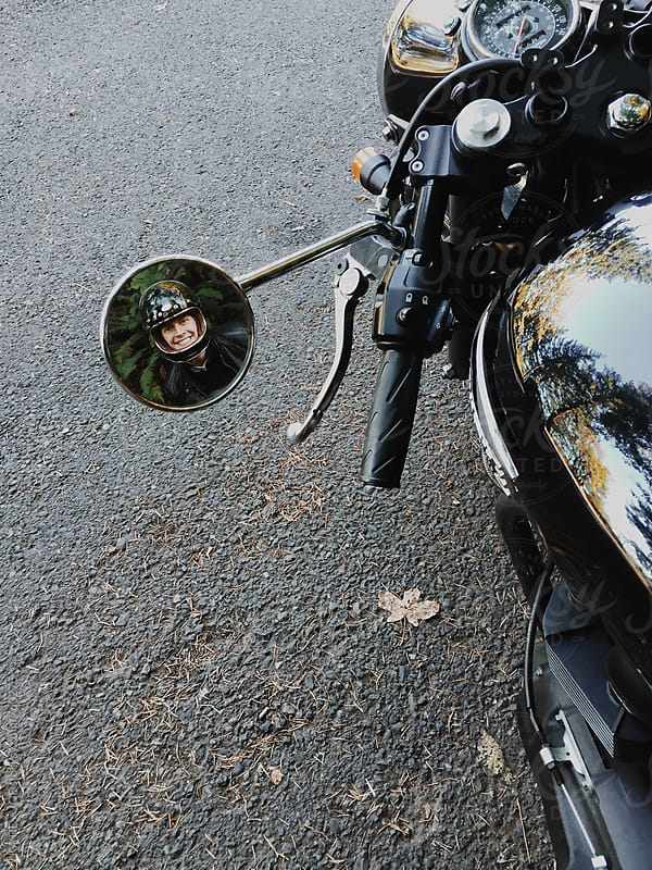 Man's head reflected in the mirror of a motorcycle by KATIE + JOE for Stocksy United