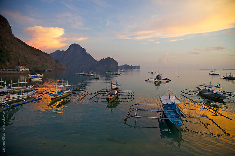 Idyllic orange sunrise on fishing boats on the harbour, El Nido, Palawan Island, Philippines by Jaydene Chapman for Stocksy United