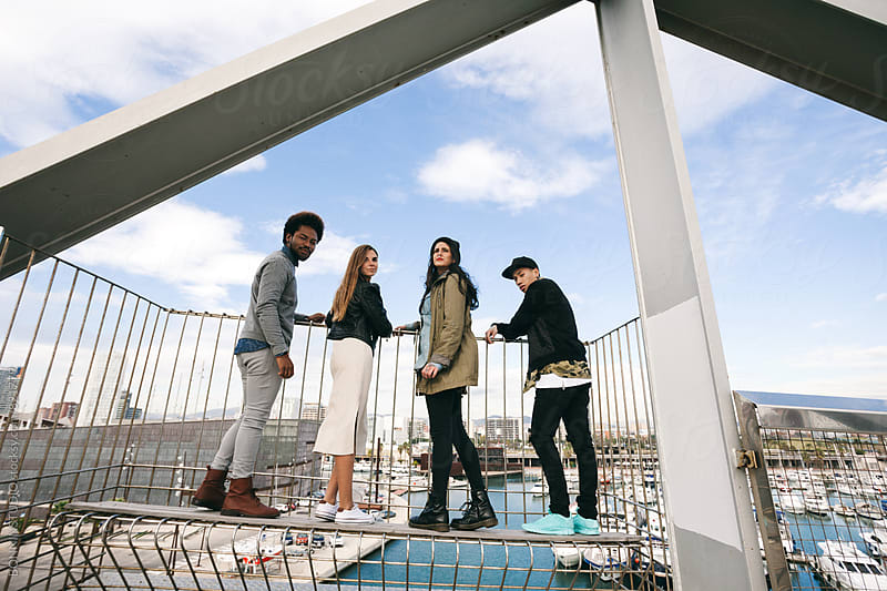 Portrait of group of friends standing on a modern bridge. by BONNINSTUDIO for Stocksy United