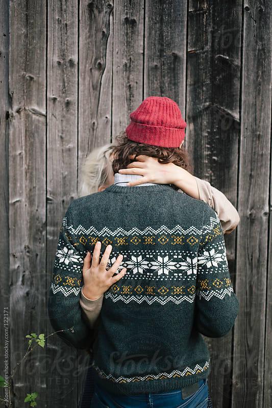 Couple in love is kissing outside against a barn. by Koen Meershoek for Stocksy United