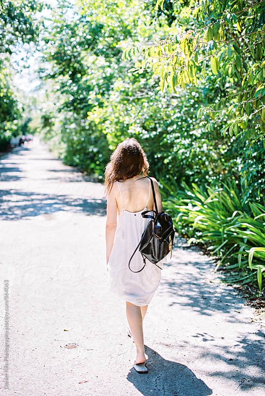 Woman walking down tropical path by Daniel Kim Photography for Stocksy United