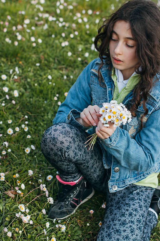 Girl collecting daisies in Spring by Beatrix Boros for Stocksy United