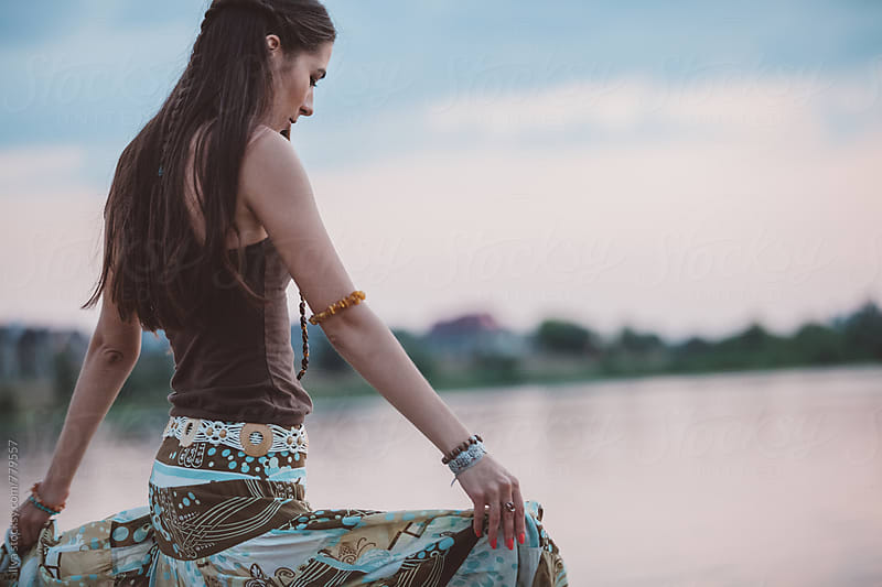 Woman in long skirt on nature in the evening by Ilya for Stocksy United