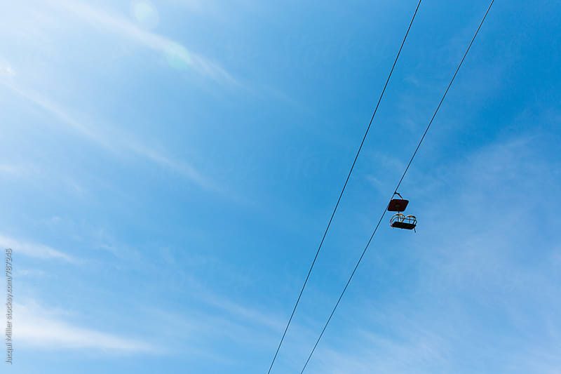 Single chair lift against a bright blue sky, with copyspace by Jacqui Miller for Stocksy United