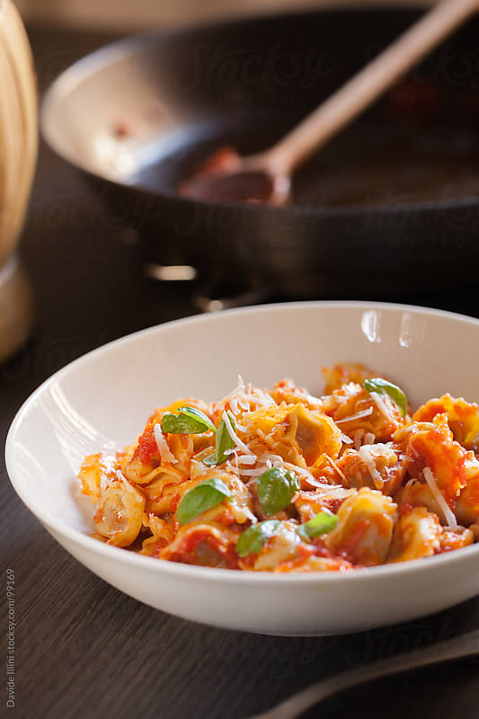 Tortellini with tomato sauce and fresh basil by Davide Illini for Stocksy United