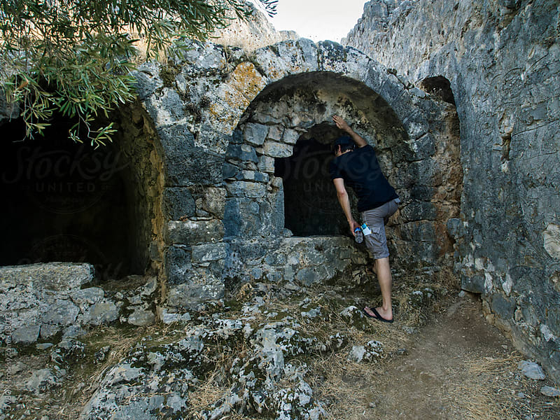 Man examining a ruined church on Gemiler Island, Fethiye, Turkey by DV8OR for Stocksy United