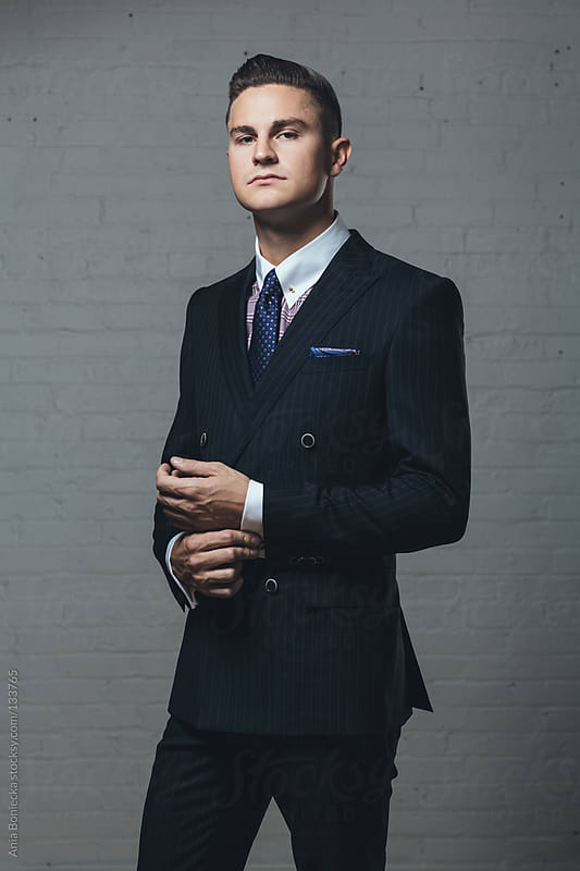 A distinguished young man in a double breasted suit adjusting his cuffs by Ania Boniecka for Stocksy United