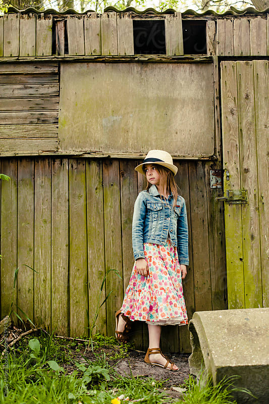 Little girl in flower dress leaning against weathered old wooden shed by Cindy Prins for Stocksy United