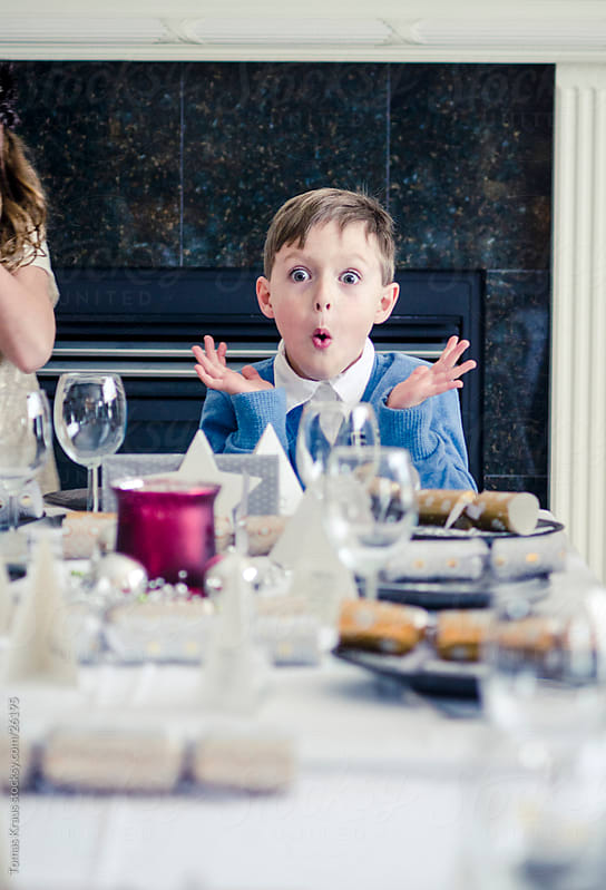 boy making a face at the dinner table by Tomas Kraus for Stocksy United