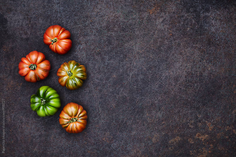 Fresh seasonal tomatoes on dark rusty surface by Paperclip Images for Stocksy United