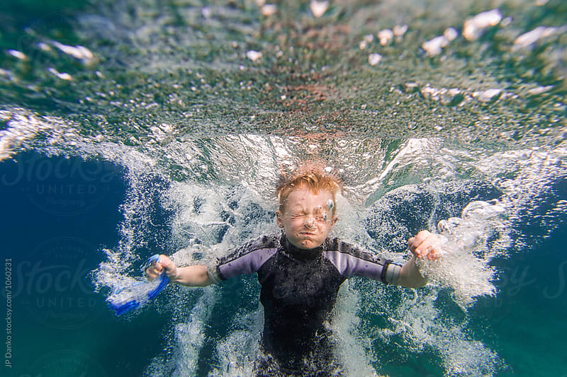 Bubbles and Underwater Splash of Boy Jumping Into Summer Lake From Water Trampoline At Cottage by JP Danko for Stocksy United
