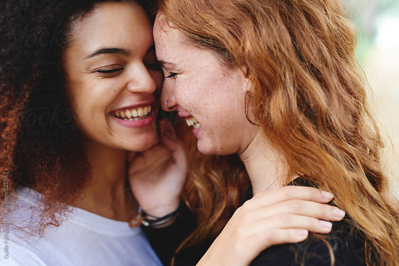 Close-up of two young girlfriends laughing by Guille Faingold for Stocksy United