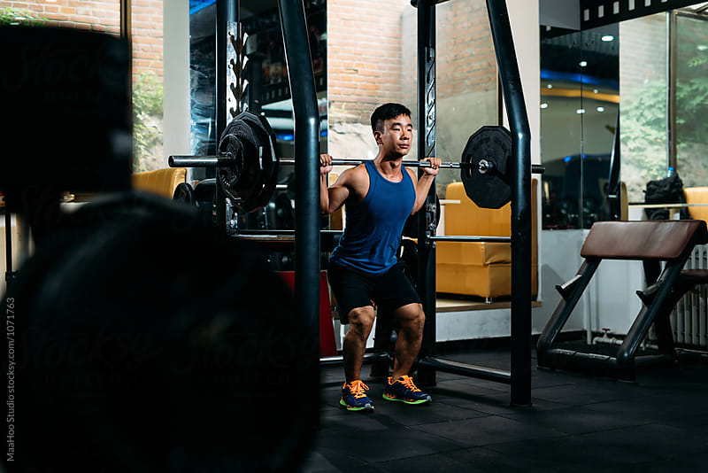 Focused man doing barbell squats at gym by MaaHoo Studio for Stocksy United