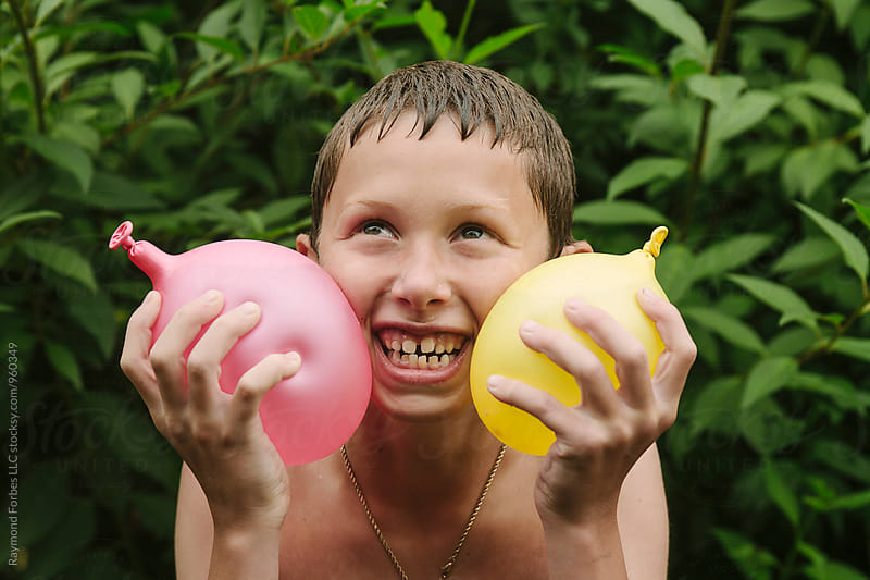 Child With Water Balloons by Raymond Forbes LLC for Stocksy United