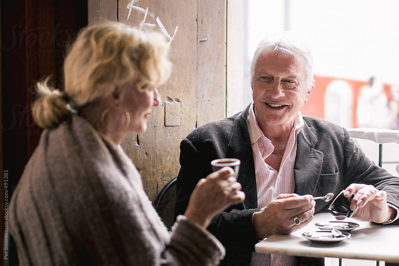 Romantic couple in their 60s in a café, drinking espresso by Per Swantesson for Stocksy United