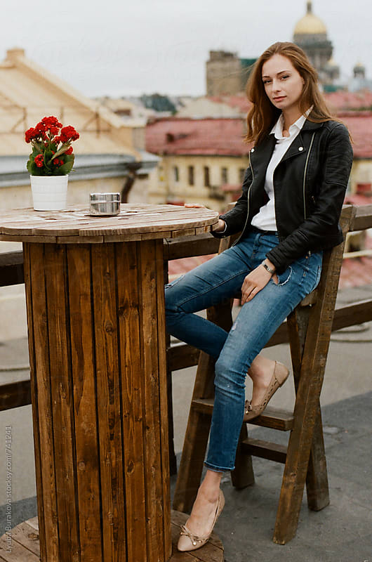 Young woman sitting in outdoors cafe by Lyuba Burakova for Stocksy United