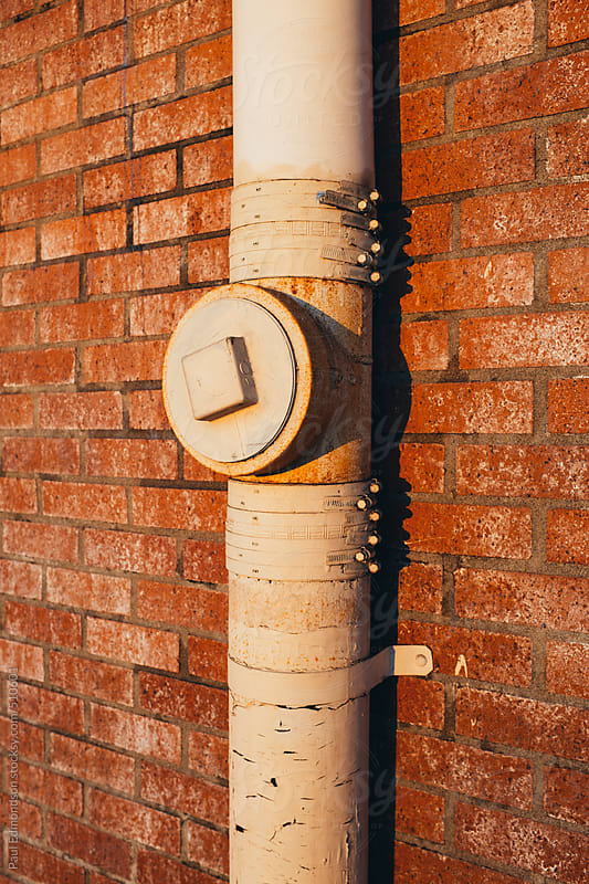 Drainage pipe extending down exterior of brick building by Paul Edmondson for Stocksy United
