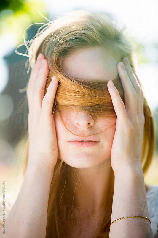 Woman hiding her eyes with hair by michela ravasio for Stocksy United