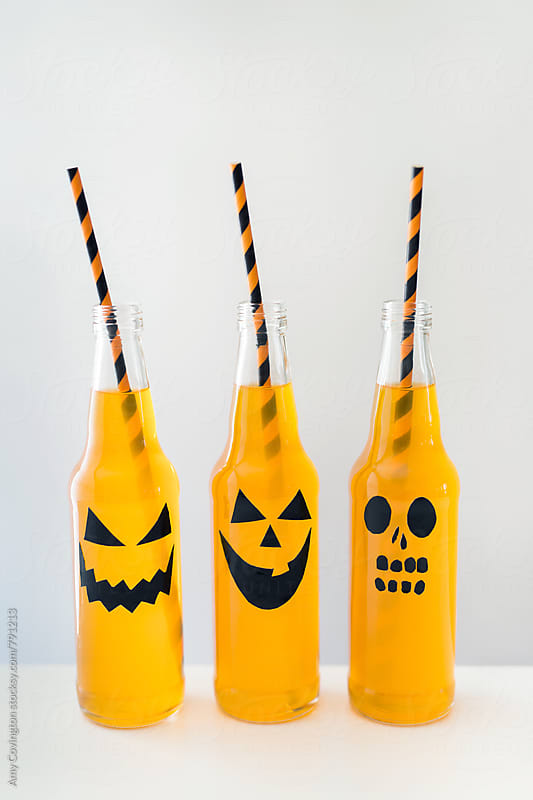 Jack-o'-lantern designs on bottled orange beverage by Amy Covington for Stocksy United