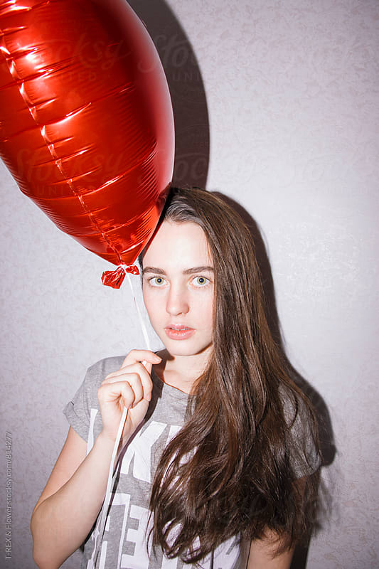 Portrait of attractive young woman holding red balloon and looking at camera by Danil Nevsky for Stocksy United