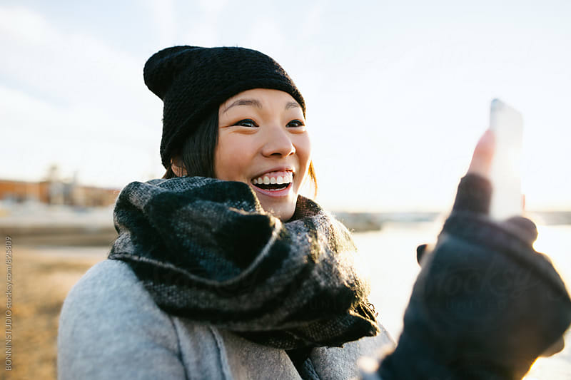Smiling woman taking a photo with her phone on the beach on winter. by BONNINSTUDIO for Stocksy United