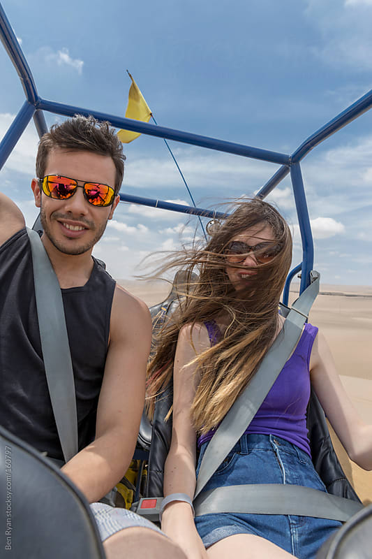 Young couple talking and laughing whilst riding a dune buggy by Ben Ryan for Stocksy United