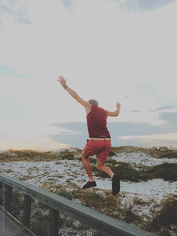 Man jumping on beach boardwalk by Nicole Mlakar for Stocksy United