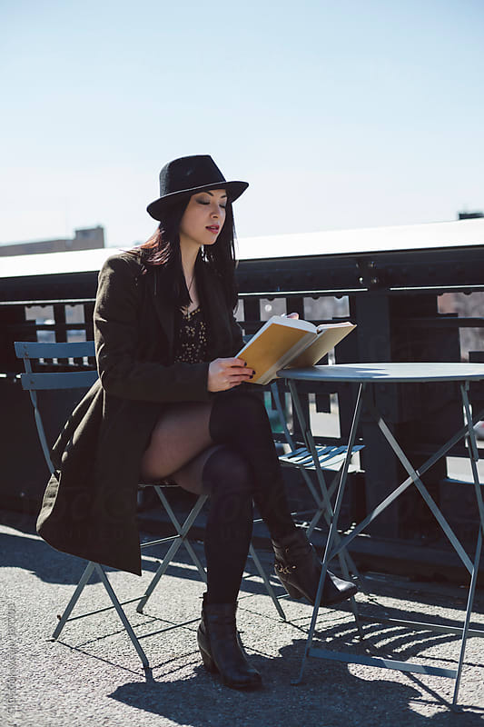 Cool young asian woman dressed in black reading a book in NYC by GIC for Stocksy United