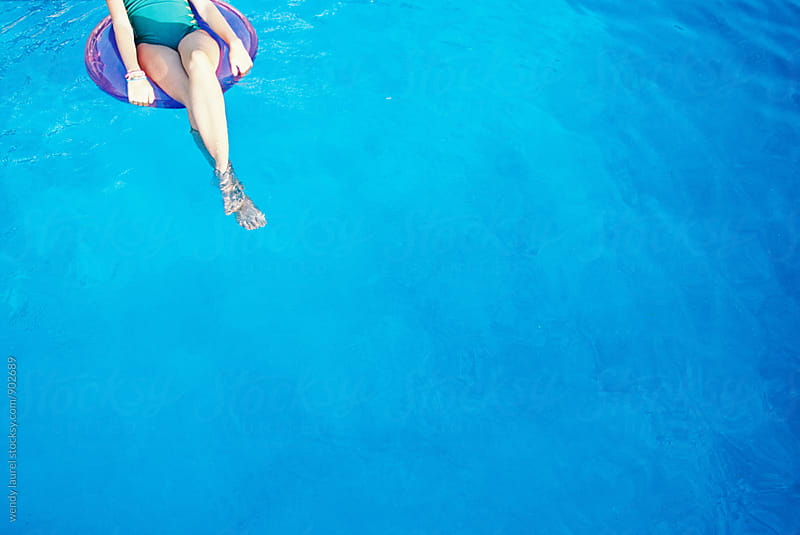 teen girls' legs in floatie in blue swimming pool by wendy laurel for Stocksy United