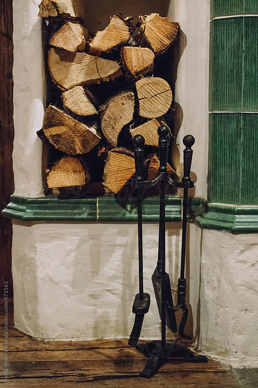 masonry heater with logs and tools by Leander Nardin for Stocksy United