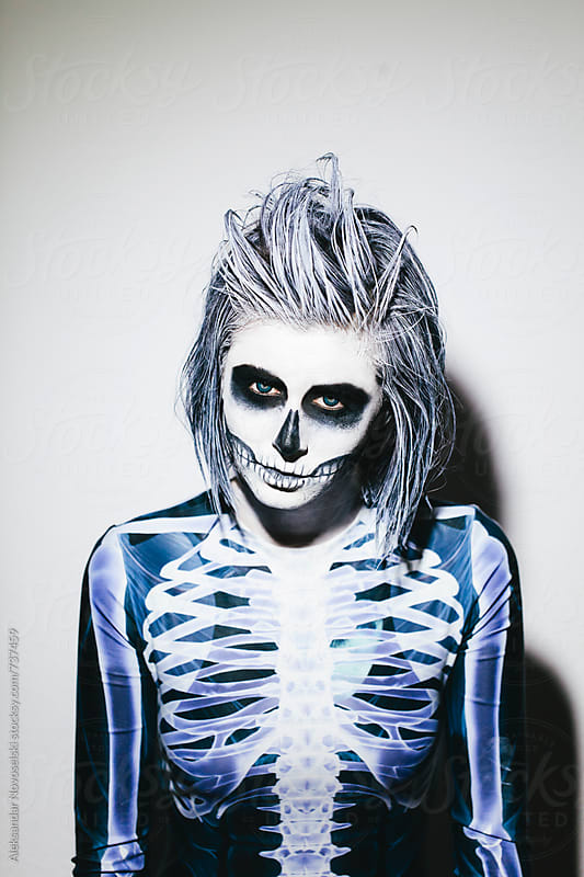 Spooky portrait of woman with skeleton costume and halloween make up on white wall by Aleksandar Novoselski for Stocksy United