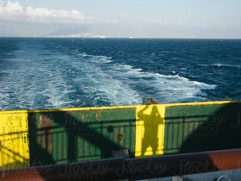 Mans shadow on back of ferry waving at ocean by Martin Matej for Stocksy United