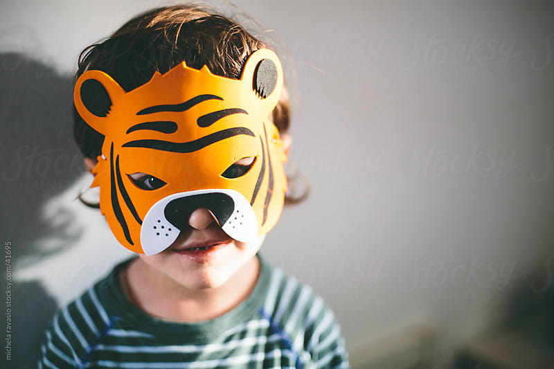 Portrait of a child with tiger mask.. by michela ravasio for Stocksy United